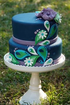 4-tier white cake with colorful peacock design and flowers, with alternating bands around the cake