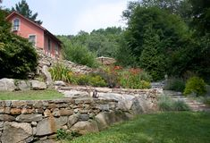 Stone retaining walls create terraces that render the steep site usable. To the right are 13  5' x 2' granite steps connecting lower garden to house.