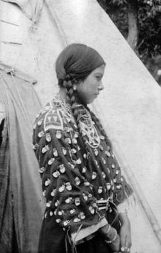 A Native American (Crow) woman, Singing Beauty, poses outdoors by a tepee near Sheridan, Wyoming. She wears a dress decorated with elk teeth, leather belt, and bead necklaces.