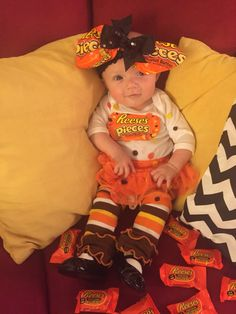 Baby homemade Reese's pieces Halloween costume! Leg warmers from etsy, made bow from two candy bags, white onesie with tiny circles of felt cut out and glued to them, and orange tutu with black Mary Jane shoes :)