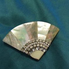 Fan Shaped Rhinestone Brooch Vintage brooch in the shape of a fan. Seems to be handmade, artisan-made costume jewelry, with mother-of-pearl onlay, tiny rhinestones, and mirror surface material on resin(?) plastic(?). Slight natural cracks within the inlay. Back has little globs of rock-hard glue: see pic #3. Sparkly and opalescent. Vintage Jewelry Brooches