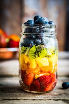 Colourful fruit salad on a jar with strawberry, orange, pineapple, kiwi and blueberry. Great idea for summer snack