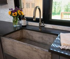 The kitchen also features a virtually undestroyable farmhouse sink made of sealed concrete. It looks really beautiful with the quartz countertop – two very durable options!