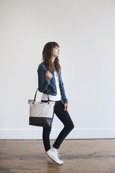 """Stay artistically stylish while on the go with this tote from Anna Joyce. Hand-painted indigo stripes pair with premium leather for a one of a kind look. Dimensions: Measures 14.5"""" x 13"""" x 4"""" Details:"""