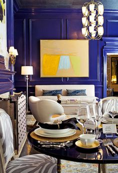 Hello, stunning blue walls, studded fireplace screen, zebra upholstered chairs... molding, chandelier, artwork, table...