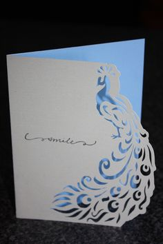 handmade card .... clean and simple design ... peacock card ... die cut bird forms the side border ... blue inner card shows through the intricate cuts ...