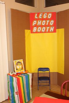 """Photo Booth fun and easy!  instructions:  1. get a yellow folding poster board at cvs, staples, home depot (ect).  2.  Make a sign that says """"lego photo booth""""  3.  Put a chair under the poster  4.  set up a table with props  5.  have someone take pictures and you are set to go!  good luck!"""