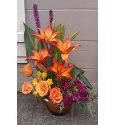 This stunning fall colored keepsake container filled with Lilies, Roses, Spray Roses, Liatris, Spray Chrysanthemums and creative foliages will please anyone. A great gift for any occasion.