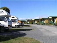 Chalets and  motorhomes near  a  welcoming hot spring pool Miranda Family Holiday Park