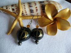 """Black Painted Kukui Nuts with Gold Honu (Turtle) with Black Shell Pearls. Featuring surgical stainless steel earwires which will never change colors. Approximately 1.0"""" long and can be worn by the most sensitive skin. FREE 24 hour SHIPPING USA ONLY."""