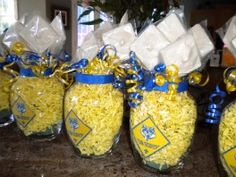 Certerpiece / favors - Blue & Gold Banquet  Consider ball quilted crystal jelly sized canning jars instead, less to fill and very inexpensive to   buy a   case. Maybe $4 for a dozen at  Walmart.   Fill with floral foam, cover with colored paper   Easter grass. Add curling ribbon.