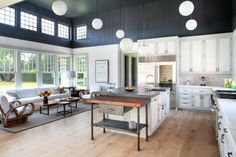A spacious two-story great room with an adjacent kitchen with a few rustic details to add charm. The upper section of the room is in navy clapboard.