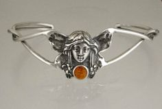 The Victorian Fairy in a Cuff Bracelet Accented with a Genuine Amber The Silver Dragon- Bracelets. $92.00. This Bracelet was Designed by The Silver Dragon, a Jewelry Shop in New England. Thank you for Supporting American Business.. Designed And Hand- Crafted in Sterling Silver. This Bracelet Fits a Standard Woman's Wrist. The Silver Dragon uses Sterling Silver that has been Reclaimed... Helping Save Mother Earth's Resources.. This Unique Bracelet is Created only after Your Or...