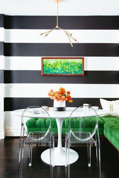 Cozinha moderna, com papel de parede listrado e cadeiras transparentes.