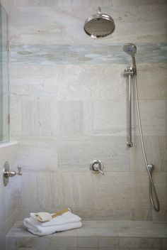 """""""My clients opted for a large, two-person walk-in shower in lieu of both a shower and free-standing tub in the space,"""" says the designer. """"With such a large shower, I carried the 12x24 tile from the floors onto the shower walls."""""""