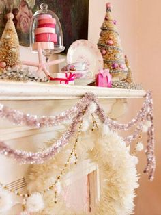 "Perfect for a cottage home, this mantel incorporates pretty vintage dishware, tinsel garland, bottlebrush trees and even a feather wreath! It is all about the ""pink."" Even a stacked roll of holiday ribbons under glass contributes to the fancifulness."