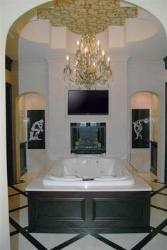 Two person tub with shower on the other side of fireplace and TV wall Victoria Martoccia Custom Homes www.shebuildsit.com