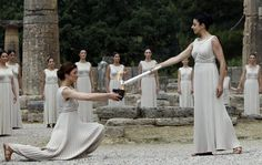 Greek actress Ino Menegaki (R), playing the role of High Priestess, lights the Olympic flame during the torch lighting ceremony of the London 2012 Olympic Games at ancient Olympia in Greece May 10, 2012