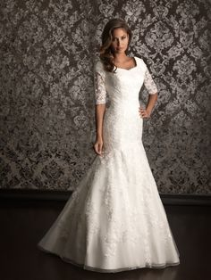 Style: M490    Lovely in lace. A slim, A-line gown featuring lace applique throughout. The bodice features a scooped neckline, 3/4 length sleeves with sheer lace details that continue to the fully covered back.   Colors:	 White, Ivory  Fabric:	 Lace Applique  Sizes:	 2 - 32