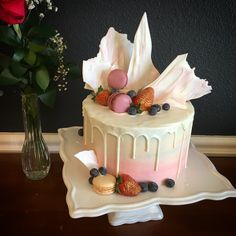 Beautiful pink and white drip cake. Chocolate with vanilla buttercream and strawberries. White chocolate shards on top.