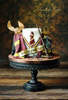 Harry Potter cake with Gryffindor school uniform, snitch and wand. By Sweetlake Cakes.