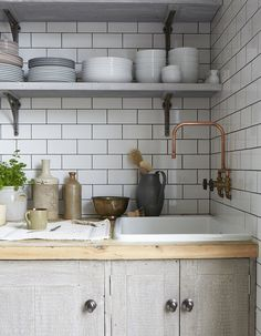 Kitchen detail in a primrose hill home, great dark grey grout on white metro tiles and use of copper pipping for tap fitting
