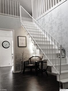 högt i tak,trapp,klocka,hörna,fåtölj,print,tavla,tapet,stålräcke,vit trappa