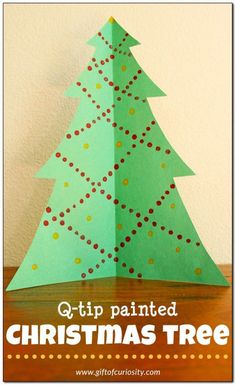 Q-tip painted Christmas tree. This is a great fine motor Christmas craft with such pretty results. These will be displayed in our living room at Christmas. || Gift of Curiosity
