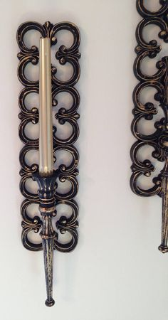 Stunning set of black & gold Syroco sconces from These were painted in black with a gold guilding paint used for the accents. Perfect for your mid century inspired decor. These sconces measure approximately inches long and are 4 inches wide.