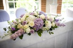 Romantic ivory and lilac wedding flowers summer wedding at Great Fosters in Surrey. Bloomy paonies, lilac Pacific Blue roses, hydrangeas & delphiniums.