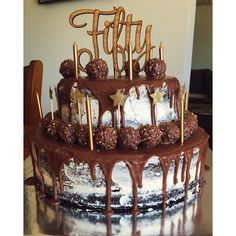 Dark chocolate naked cake with vanilla frosting and milk chocolate dripping. 50th cake for males.