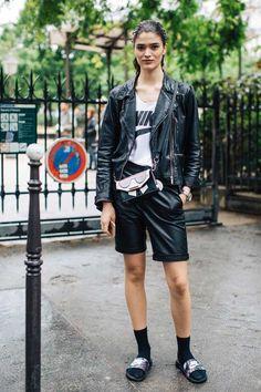 Look combinando bermuda e jaqueta de couro, camiseta, meia alta e slide.
