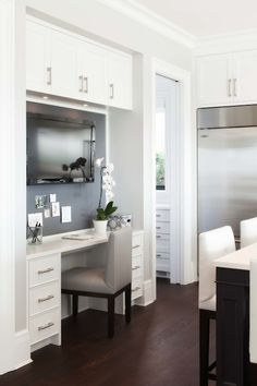 Gorgeous kitchen with office space featuring flatscreen TV over desk paired with gray leather chair.