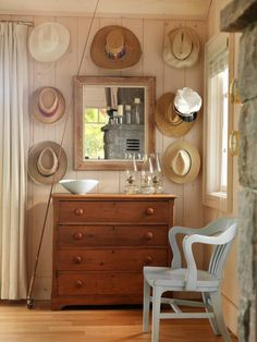 This rustic paneled living room features a classic chest of drawers and a mirror surrounded by hats hung on the wall. As seen on HGTV.