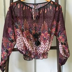Bebe top This top is sheer. It is so pretty. The colors are warm and girly. The tassels are so fun! They are pictured above. The bottom is cinched to be tight on the waist. Long sleeves. The shirt says xs but it could fit a small possibly. bebe Tops