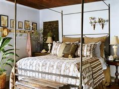 This hard iron bed is softened with layers of rich contrasting fabric covers and pillows. Coat hooks mounted on the wall, at left, add cottage style to the room
