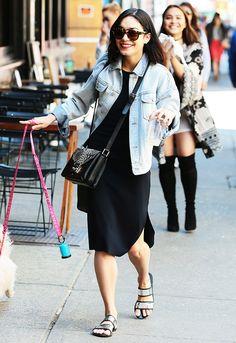 Vanessa Hudgens in a denim jacket, black dress, silver sandals, black bag, and sunglasses