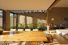 O pergolado (ao fundo) tem estrutura de concreto aparente no projeto do escritório Anastasia Arquitetos. A pérgola se projeta sobre uma área verde interna e oferece luz natural e ventilação ao jardim, além de melhorar o conforto térmico das salas adjacentes.  Fotografia: Jomar Bragança /  Divulgação.  http://estilo.uol.com.br/casa-e-decoracao/album/2016/09/04/pergolados-criam-sombra-e-deixam-o-jardim-e-ate-areas-internas-mais-bonitas.htm?foto=3