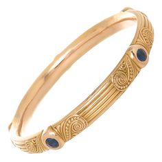 Riker Brothers Sapphire Gold Bangle Circa 1910. Circa 1910 14K Yellow Gold Bangle Bracelet by Riker Brothers, with strong aesthetic design work and set with Fine Blue Sapphires, possibly of Montana origin. A great piece from the best era of American jewelry Manufacturing and in Pristine condition. Inside diameter just over 7 inch.