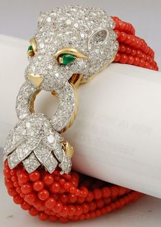 David Webb lion head bracelet in gold, platinum, and enamel with diamonds, emeralds, and coral beads. Via 1stdibs.