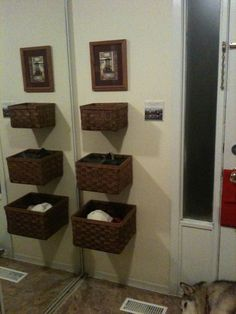 Baskets hung in a front hall.  Children can reach the lower ones easily for hats and scarves!