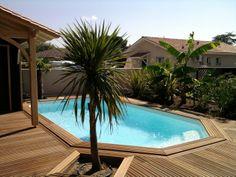 Piscine de forme octogonale encastrée dans une terrasse composée de planches de bois clair.
