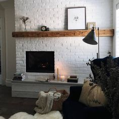 The fireplace and the picture on the shelf balance each other out. The dark couch/arm chair with the lamp also balance out the fireplace.