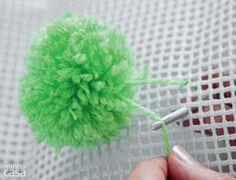 Prenda o primeiro deles no centro da tela: com a agulha de crochê, passe as pontas do fio pela tela, deixando um intervalo de pelo menos dois buraquinhos entre elas, e faça dois nós.