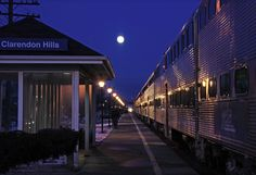 Westbound Metra train No. 1249 stops under the rising moon at Clarendon Hills, Ill., on Metra's BNSF Railway line. Two additional trains are visible about a mile away in the distance.   Photo by Paul Hoffmann
