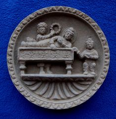 """A finely carved Gandharan schist """"cosmetic tray"""" measuring about 11.5 cm diameter.  This is usually interpreted as a banquet scene where Buddha (indicated by his aura and cranial bump) is attended by two women.  He lies on what is known as a kline, a type of couch.  The woman at the left has either a fan or a wreath.  This scene is also sometimes interpreted as a funerary scene, although traditionally Buddha lies on his right side in Parinirvana."""