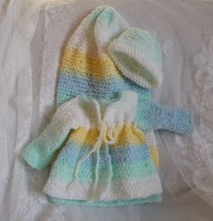 This crocheted baby cocoon with sweater and matching hat was made with a Baby Cuddles yarn - a nice soft textured yarn that is washable. The texture is like a soft terry cloth. The sweater is super warm along with the matching hat. The sweater can even be worn as a coat.  The colors are blue, mint, yellow and white.  This set is washable.  The above item is ready to ship within 3-5 days. Please see my policies regarding custom made products.  Be sure to contact me if you are making more…