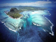 Approximately 1,200 miles off the southeast coast of Africa lies an island nation known as Mauritius that gives off the illusion of an underwater waterfall at the southwestern tip of the island. The visually deceiving impression, created in the water due to the runoff of sand and silt deposits, is especially effective and breathtaking in aerial shots.
