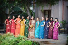 The bridesmaids all look great in their traditional Indian saris, giving each bridesmaid a different bold color. It's like a rainbow of bridesmaids.