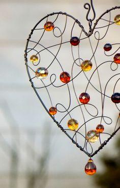 """Suncatcher. Suncatcher.....je určený k zavěšení do okna, kde jím budou prostupovat paprsky slunce, které přinesou do místnosti klid a harmonii..... Tuto variaci na lapač slunečních paprsků neboli """" suncatcher"""" jsem vyrobila z černého drátu a broušených perlí karamelovývh barev. Rozměr srdíčka: 20 x 21 cm Délka včetně háčku pro zavěšení: 50 cm Ošetřeno antikorozním ..."""